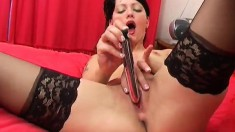 Enticing brunette in black stockings uses a dildo to make herself cum