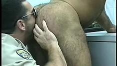 Handsome policeman gets a horny prisoner to suck his sausage