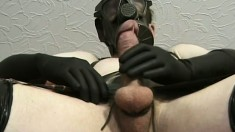 Kinky stud in a latex costume and a gas mask pleases his long cock