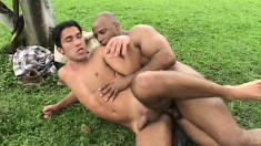 Horny Latino has a muscled black dude pounding his butt hole outside